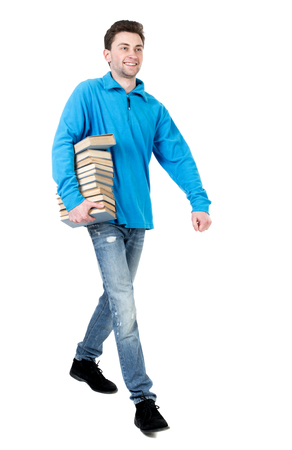 treading: side view of going  man carries a stack of books. walking young guy . Rear view people collection.  backside view of person.  Isolated over white background. The curly-haired student in a blue sweater is warm smile passes with books. Stock Photo