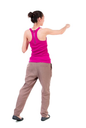 back view of woman funny fights waving his arms and legs. Rear view people collection. backside view of person.  Isolated over white background. dark-skinned girl in a red t-shirt boxing. Stock Photo