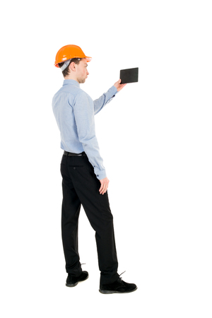 Backview of business man in construction helmet stands and enjoys tablet or using a mobile phone. Standing young guy. Rear view people collection.  backside view of person.  Isolated over white background. Curly businessman in a light jacket and a helmet