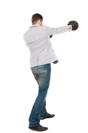 businessman with boxing gloves in fighting stance. Isolated over white background. Rear view people collection.  backside view of person. A guy in a gray jacket boxing gloves. Stock Photo