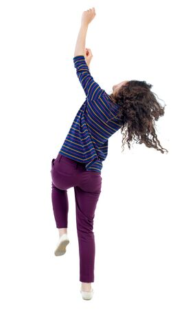back view of dancing young beautiful  woman. girl  watching. Rear view people collection.  backside view of person.  Isolated over white background. Long-haired curly girl in blue blouse is actively moving to the music.