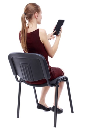 back view of woman sitting on chair and looks at the screen of the tablet.  Rear view people collection.  backside view of person.  Isolated over white background. A girl in a burgundy dress sitting on a chair and working with plashnetom. Stock Photo