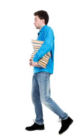 side view of going  man carries a stack of books. walking young guy . Rear view people collection.  backside view of person.  Isolated over white background. The curly-haired student in a blue warm jacket carries books. side view.