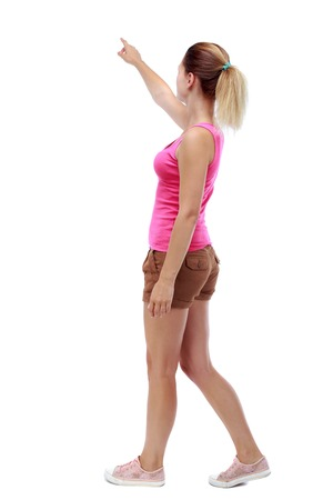 back view of pointing walking  woman. going girl pointing.  backside view of person.  Rear view people collection. Isolated over white background. Sport blond in brown shorts is by pointing to the sky.