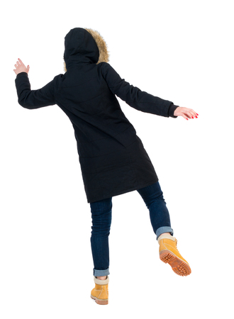 slipped: Back view woman in winter jacket  Balances waving his arms.   Standing young girl in parka. Rear view people collection.  backside view of person.  Isolated over white background. Girl in warm winter black jacket slipped and falls to the side.