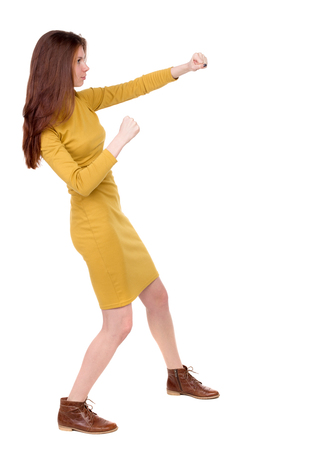 loser: skinny woman funny fights waving his arms and legs. Isolated over white background. Long-haired brunette in a mustard-colored dress hands fights.