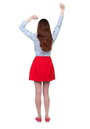back view of dancing young beautiful  woman. girl  watching. Rear view people collection.  backside view of person.  Isolated over white background.Long-haired brunette in red skirt lifted up his fists.