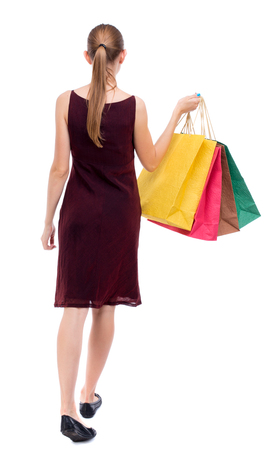 sleeveless dress: back view of going  woman  with shopping bags . beautiful girl in motion.  backside view of person.  Rear view people collection. Isolated over white background. The girl in the maroon sleeveless dress holding shopping bags. Stock Photo