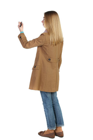back view of writing beautiful woman. Rear view people collection.  backside view of person. Isolated over white background. The blonde in a brown coat paints a felt-tip pen plan Stock Photo