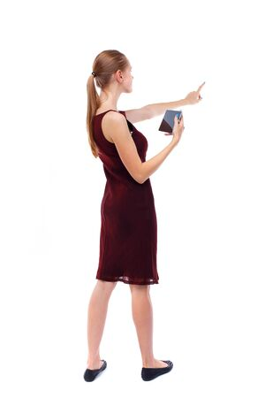 girl in burgundy dress: back view of pointing young beautiful  girl with tablet computer. girl  watching. Rear view people collection.  backside view of person.  Isolated over white background. Slim blonde in a burgundy dress holding a tablet and shows his hand forward.