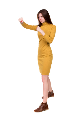 loser: skinny woman funny fights waving his arms and legs. Isolated over white background. Long-haired brunette in a mustard-colored dress in boxing.