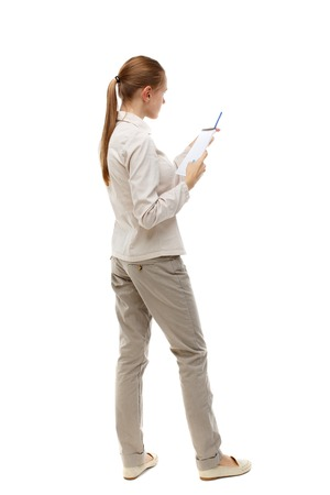 instructs: back view of  stands woman takes notes in a notebook. girl  watching. Rear view people collection.  backside view of person.  Isolated over white background. Skinny girl in white denim suit instructs reading from a notebook.