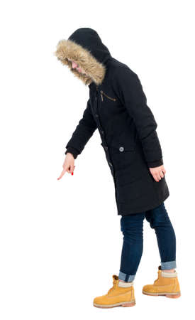 Back view of  pointing young women in parka. Young girl gesture. Rear view people collection.  backside view of person.  Isolated over white background. The girl in warm winter jacket is black with cancer and is pointing down.