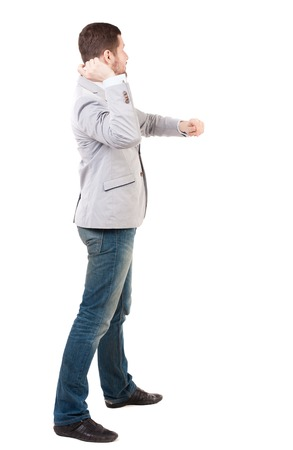 back view of guy funny fights waving his arms and legs. Isolated over white background. Rear view people collection.  backside view of person. A guy in a gray jacket waving his arms.