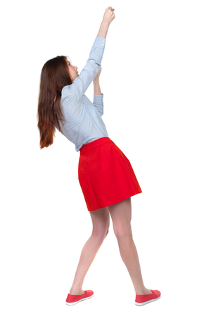 back view of standing girl pulling a rope from the top or cling to something. girl  watching. Rear view people collection.  backside view of person.  Isolated over white background. Long-haired brunette in red skirt hung on a rope. Stock Photo