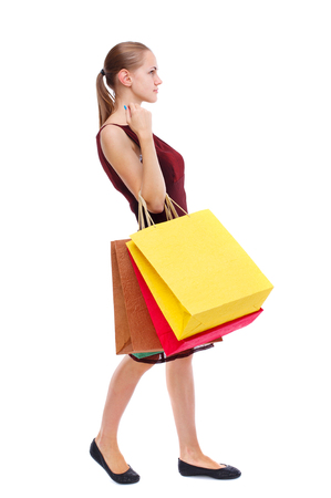 side view of going  woman  with shopping bags . beautiful girl in motion.  backside view of person.  Rear view people collection. Isolated over white background. Slim blonde in a burgundy dress carries a paper bag. Stock Photo