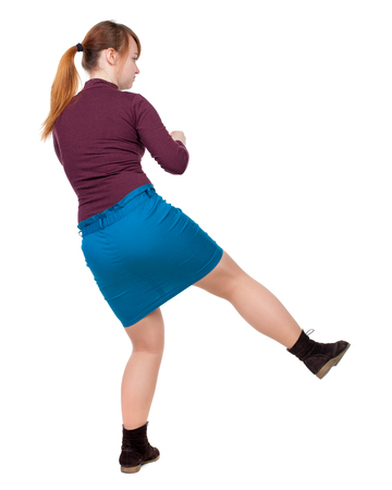 skinny woman funny fights waving his arms and legs. Isolated over white background. The red-haired girl in a blue skirt leg beats. Stock Photo