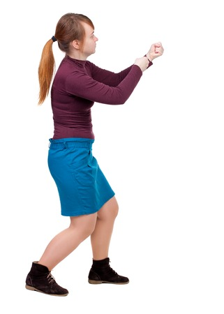 back view of standing girl pulling a rope from the top or cling to something. girl  watching. Rear view people collection.  backside view of person.  Isolated over white background. Red-haired girl pulls the rope in a blue skirt.