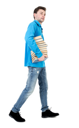 striding: side view of going  man carries a stack of books. walking young guy . Rear view people collection.  backside view of person.  Isolated over white background. The curly-haired student in a blue warm jacket comes with books and looking at the camera.
