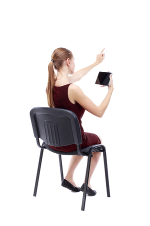 girl in burgundy dress: back view of pointing woman sitting on chair and looks at the screen of the tablet.  Rear view people collection.  backside view of person.  Isolated over white background. A girl in a burgundy dress sitting on a chair looking at the tablet and pointing h