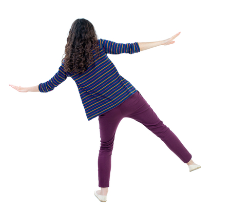 Balancing young woman.  or dodge falling woman. Rear view people collection.  backside view of person.  Isolated over white background. Long-haired curly girl in a blue striped sweater balances on one leg. Stock Photo