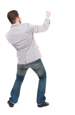1 person: back view of standing man pulling a rope from the top or cling to something.  Rear view people collection.  backside view of person.  Isolated over white background. A guy in a gray jacket, pulls a rope from the top Stock Photo
