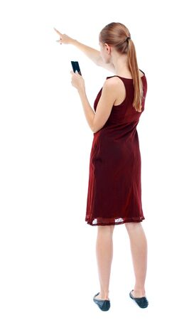 girl in burgundy dress: back view of pointing young beautiful  girl with tablet computer. girl  watching. Rear view people collection.  backside view of person.  Isolated over white background.  A girl in a burgundy dress sleeveless photographs on the phone and showing thumb. Stock Photo
