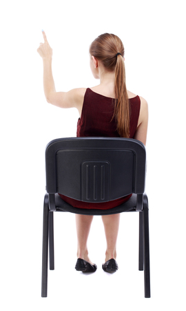 girl in burgundy dress: back view of young beautiful  woman sitting on chair and pointing.  girl  watching. Rear view people collection. A girl in a burgundy dress sitting on a chair and presses his finger on the button.