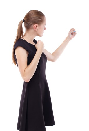 wimp: skinny woman funny fights waving his arms and legs. Isolated over white background. Blonde in a short black dress clenched her fists.