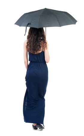 young woman in dress walking under an umbrella. Rear view people collection.  backside view of person.  Isolated over white background. The dark curly girl in blue evening dress went off under a black umbrella.