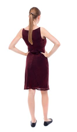 girl in burgundy dress: back view of standing young beautiful  woman.  girl  watching. Rear view people collection.  backside view of person. A girl in a burgundy dress sleeveless standing with hands on waist. Stock Photo