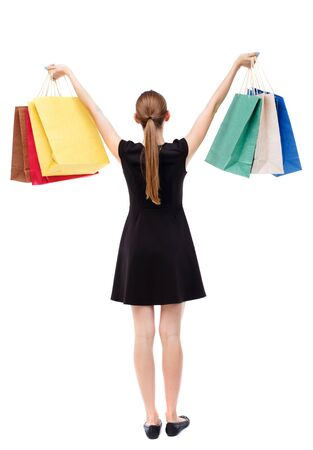 holding aloft: back view of woman with shopping bags. backside view of person.  Rear view people collection. Isolated over white background. Blonde in a short black dress holding aloft shopping bags. Stock Photo