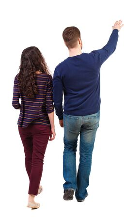 Back view of walking young couple (man and woman) pointing. Rear view people collection. backside view of person. Isolated over white background. Swarthy girl and the bearded man on the move shows his hands up.