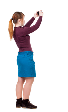 back view of standing young beautiful  woman  and using a mobile phone. girl  watching. Rear view people collection.  backside view of person.  Isolated over white background. Girl with red hair tied in a ponytail relieves phone.