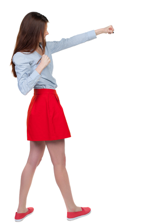 skinny woman funny fights waving his arms and legs. Isolated over white background. Long-haired brunette is cancer and has boxed in a red skirt