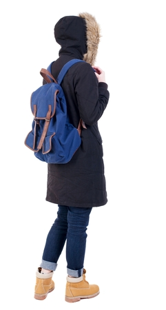 parka: Back view woman in winter jacket with a backpack  looking up.   Standing young girl in parka. Rear view people collection.  backside view of person.  Isolated over white background. Stock Photo
