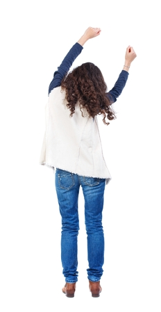 sways: back view of dancing young beautiful woman. Long-haired girl with curly hair sways in time with the music.