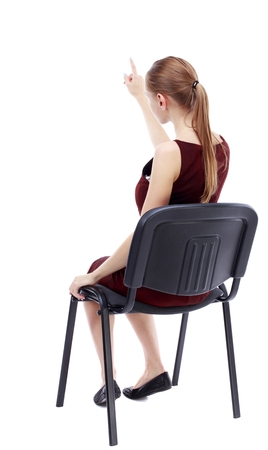 girl in burgundy dress: back view of young beautiful woman sitting on chair and pointing. girl in a burgundy dress sitting on a chair finger pointing. Stock Photo