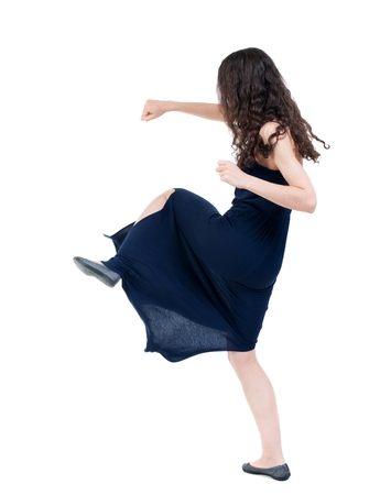 skinny woman funny fights waving his arms and legs. dark curly girl in blue evening dress fights. Stock Photo