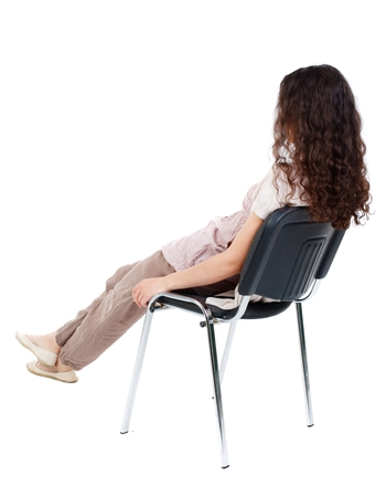reclining chair: back view of young beautiful woman sitting on chair. Isolated over white background. Long-haired curly girl sitting on a chair reclining. Stock Photo