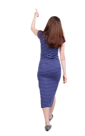 observes: back view of pointing walking woman. going girl pointing. backside view of person. brunette in a blue striped dress went off showing thumb up.