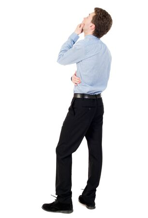 dreaminess: back view of standing business man. curly-haired businessman in light shirt looking up thoughtfully. Stock Photo