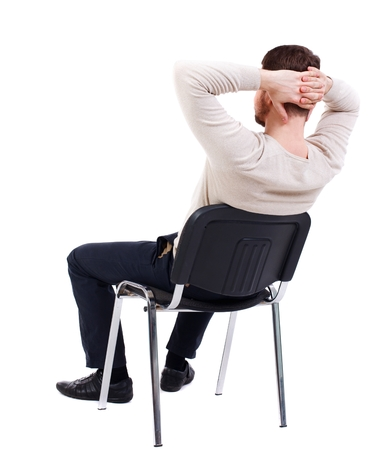 head and  back: back view of business man sitting on chair. bearded man in a white warm sweater sits on a chair with his hands behind his head. Side view. Stock Photo