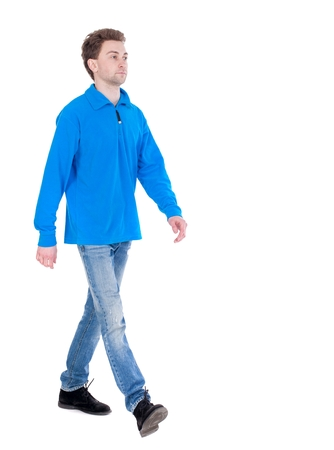 treading: front view of going handsome man. walking young guy . Rear view people collection. Curly boy in the blue jacket comes to meet us.