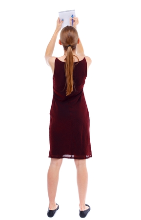 girl in burgundy dress: back view of stands woman takes notes in a notebook. girl watching. Isolated over white background. Slim blonde in a burgundy dress writes in a notebook.