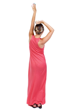 back view of dancing young beautiful woman. girl watching. A slender woman in a long red dancing waving his arms above his head. Stock Photo