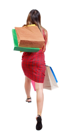 red plaid: back view of a woman jumping with shopping bags. girl in red plaid dress jumping holding a gift paper bags.