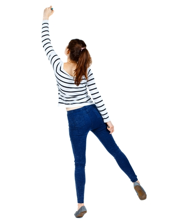 tiptoes: back view of writing beautiful woman. Rear view people collection. Girl in a striped sweater standing on tiptoes and draws marker.