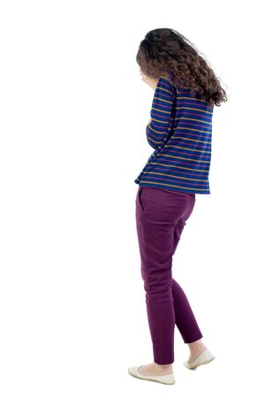 observes: back view of walking woman. Long-haired curly girl in a blue jacket crying