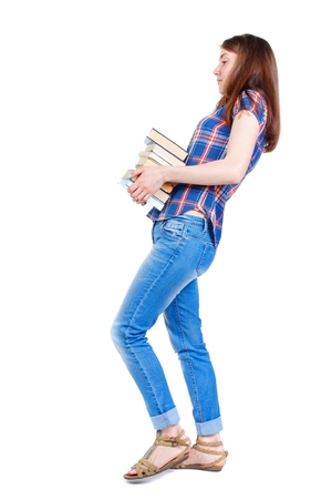 Girl comes with stack of books. side view. Girl in a plaid shirt goes to the side with a stack of heavy books. Stock Photo